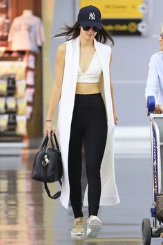 At New York's JFK airport, Jenner jet-sets in style wearing a long white vest and plunging crop top with her casual black leggings and sporty cap and sneakers.