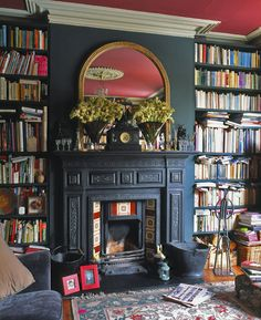 Dark walls, dark book case round fireplace
