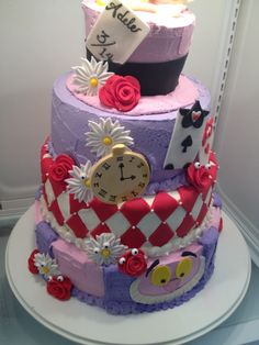 Alice in Wonderland theme baby shower cake. White cake strawberry cake and chocolate cake tiers with chocolate chip cream filling. Cake iced in buttercream with fondant decorations and a white chocolate tea cup saucer and spoon on top.