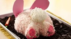 This chocolate cake, topped with vanilla butter cream and covered with pink dyed shredded coconut, sits above a bed of chocolate cookie crumbed dirt.