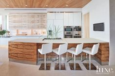 The kitchen's striking design is marked by a combination of bleached and natural koa veneers, which were executed by Brassington Caseworks, and frosted glass cabinetry from DNA Design Group. The appliances are by Miel.