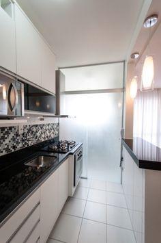 !!!!A cozinha se integra à sala através do balcão com tampo em granito Preto São Gabriel. O mesmo da bancada com a pia e cooktop. Painel de correr em vidro jateado, separa a cozinha da área de serviço.