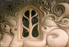 This stunningly beautiful window, in sculpted cob walls, looks out from a tiny home that sits on the banks of a small stream in Somerset, England.