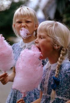 Girls eat large swirls of cotton candy in Copenhagen, Denmark, January 1963