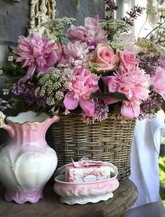 Variety of pink flora in wicker basket on bathroom table with lovely water pitcher and matching pink soap dish.