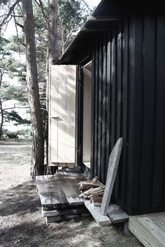 Wooden cabin in Sweden by Septembre Architecture containing a sauna and a bedroom with large picture windows that frame views of the surrounding forest. Board And Batten Cladding, Wooden Facade, Wooden Cabins, Dream Beach Houses, Green Colour Palette, Garden Studio, Forest House, Cabins And Cottages, Dark Stains