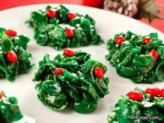 Holly Crackles. No bake. 1 stick butter  30 large marshmallows (just under 1 10oz bag)  green food coloring  vanilla extract  4c cornflakes cereal  red candies for decorating. Mom used to make these!..