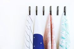 Today there are so many adorable tea towel designs that go beyond basic colors. They can become part of your kitchen design with a few spray painted clothing pins on the wall...