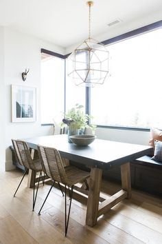 Cozy Kitchen Nook | rectangular table with modern wicker chairs | glass and gold pendant light | large window over banquette