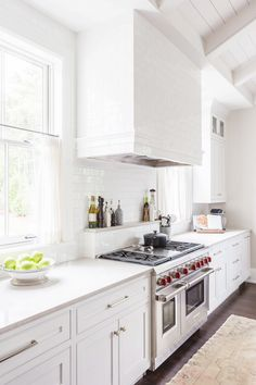 Contemporary all-white kitchen with white backsplash, white cabinents, dark wood floors, and a runner rug