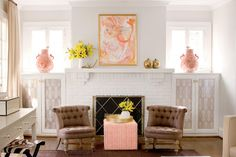 Over this fireplace, a painting by the homeowner's aunt provides playful color inspiration. Its coral hues are repeated in fabrics and accessories. Wallpaper remnants are placed inside the built-in glass cabinets to hide DVDs and toys and provide an inexpensive style fix.  See this 1920's Home