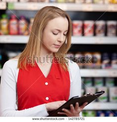 Beautiful saleswoman reading checklist on clipboard in grocery store