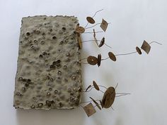 book with gestures of leaving by Ines Seidel, concrete, peas, wire, cardboard shapes from firecrackers