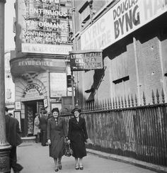 """Soho, London c.1945: A different type of variety show was provided by """"The Windmill Theatre"""", which became famous for its daring tableaux vivants and non-stop revue called """"Revudeville"""". It was also the only theatre in London to remain open during the height of the Blitz, a fact it proudly proclaims on the sign visible in this photograph above the theatre's entrance: 'we never closed' (or """"we never clothed"""" as the wags would have it)."""