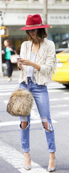 Arielle Nachami is wearing ripped jeans from Levis, shoes from Christian Louboutin, T-shirt from James Perse, white fringe jacket from Tularosa, hat from Otte and the bag is from Theory