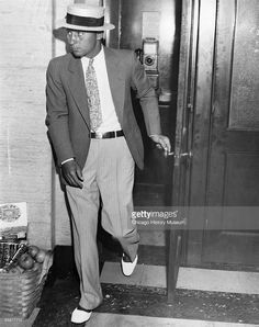 Longtime Capone enforcer and bodyguard 'Machine Gun' Jack McGurn is seen leaving a phone booth at an unidentified location in Chicago, ca.1920s.
