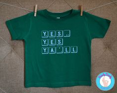 "This trendy tee is exactly what your cool little one needs. Our made-to-order shirt features light blue scrabble-style lettering on a kelly green onesie bodysuit or toddler t-shirt. The text reads Yes, Yes, Yall.  All of our products are made to order on a professional heat press. If you'd like a different color combination (see image showing our options), include that info in the ""notes to seller"" section when you are making your purchase, otherwise shirt will be created as pictured.  Be…"