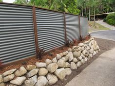 Boulder rock retaining wall w/ hardwood posts and colorbond corrugated iron fence