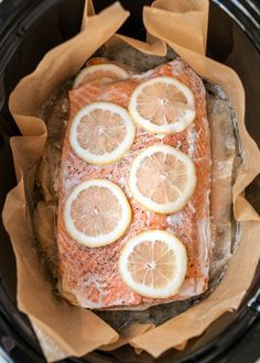 Line your cooker with parchment paper or foil and place the salmon in. Season with aromatic herbs like dill, rosemary, and thyme.
