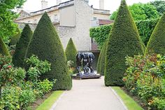 Rodin's Art of Pleasure and Knowledge is ringed with cone-shaped boxwoods. The layout encourages visitors to circle around the work of art.