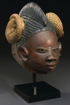 Yoruba Gelede Mask, Nigeria - Yoruba Gelede Helmet Mask, Nigeria height 15 1/4in (38.5cm) of deeply hollowed form and pierced around the edges for attachment, the single-crested coiffure dividing two coiled pangolins above an elliptical facial plane with pierce almond-shaped eyes, flaring nostrils and pursed lips; fine, honey-brown patina with indigo, red, black and yellow pigments.