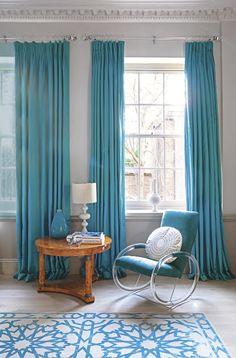 Puddling silk curtains, plush velvet seat, pear-drop ceramic vase and patterned oriental rug.