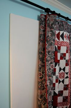 Hang quilt over design wall from curtain rod with clips!  ❤