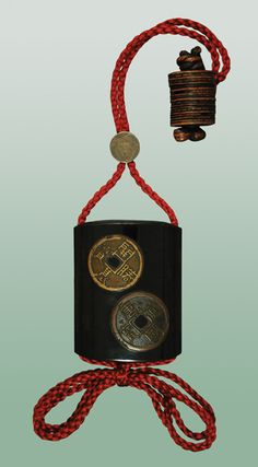 A four case roiro lacquer inro decorated with three takamaki-é archaistic coins of simulated metal with textured surface and intentional attrition. Coins in Japanese art invariably symbolize wealth and prosperity. Mid 19th Century. This inro is accompanied by an excellent netsuke of stacked coins secured by a knotted cord. Early 19th Century. Silver ojimé with engraved fuji kiku blossom.