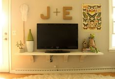 Not the styling (although cute for a play room) Each family member's initial on the tv wall.