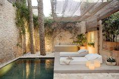 aménagement petit jardin dans l'arrière-cour avec deux chaises longues blanches, piscine et ouvent