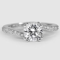 This setting features a gorgeous band of pavé-set diamond accents that gracefully swirl around the prong-set center diamond.