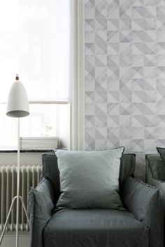 Swedish soft modern living room with grey geometric wallpaper.