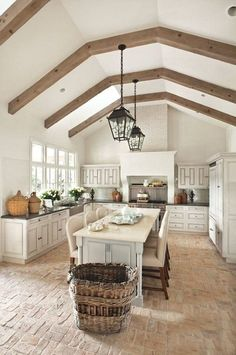 Airy French country-style kitchen with brick floors, iron pendant lanterns and exposed wood beams in the slanted ceiling.