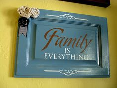 """Family is Everything"" on a repurposed cabinet door. An easy way to add to a photo gallery wall."