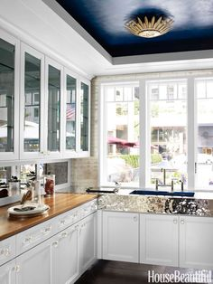 In the butler's pantry of our 2012 Kitchen of the Year designed by Mick De Giulio, a gold Apollo light fixture by Suzanne Kasler for Circa Lighting, pops off the deep sapphire ceiling.