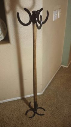 Coat rack made from recycled horseshoes and an old wooden shovel handle. Americanmetalart.net