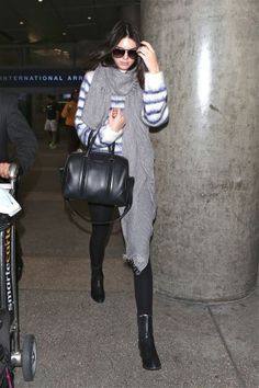 50 Airport Outfits to try: Kendall Jenner in a fuzzy stripe sweater, long gray scarf + black skinny jeans and ankle boots