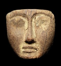 An Egyptian wood mummy mask  Late Period, circa 664-332 B.C. The facial features schematically carved, the eyes raised, some evidence of painted gesso remaining,