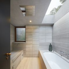 Another fantastic example of a modern bathroom, wrapped in wood-look porcelain tiling. The lengthy oval soaking tub is also encased in the wood-look tile. A skylight above the soaking tub and a window tucked in a nook to the left provide ample lighting.