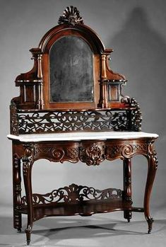 Victorian Rococo Revival Carved And Grained Rosewood Duchesse (Dressing Table), Arched Crest  Centering Shell Over Adjustable Mirror Flanked By Shelves, Shaped Shelf Above Fretwork Gallery, Shaped Marble Top, Conforming Frieze Fitted With Drawer Centered By Latticework Shell, Cabriole Legs, Stretcher Shell With Fretwork Gallery - American    c.1840-1870  -  Prices4Antiques