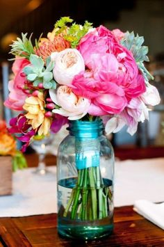 Love the look of bigger flowers in the mason jars. Jars could be tinted for center pieces