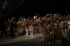 Vladislav Tretyak (R) carries the Olympic torch with Irina Rodina during the Opening Ceremony of the Sochi 2014 Winter Olympics at Fisht Oly...