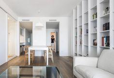 Una parete attrezzata a libreria avvolge il living open space, che comprende la zona dedicata ai pasti, illuminata dalla lampada a sospensione Paul Neuhaus in versione bianca, e il salotto con affaccio alla terrazza