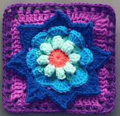This Blooming Daydreams Granny Square is a floral fantasy! Worked up in deep jewel tones with worsted weight yarn, this crochet granny square features a raised and textured crochet flower surrounded by simple crochet stitches, worked in rounds.