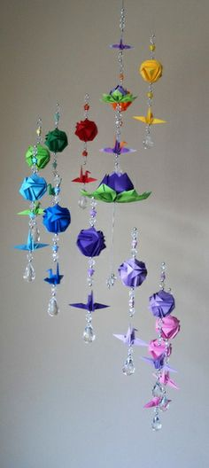 12 tsurus, 12 kusudamas pequenas, 24 mini estrelas, 2 flores de Lótus em tamanhos diferentes (a cor das flores de Lótus podem variar de acordo com a disponibilidade de papéis), tudo em papel importado, aro de madeira forrado com fita de seda, pingentes e miçangas em acrílico. Dimensão 26 cm de largura e 90 cm de altura. OBS. : OS PINGENTES E AS ESTRELAS PODEM VARIAR DE ACORDO COM O MATERIAL DISPONÍVEL R$ 130,00
