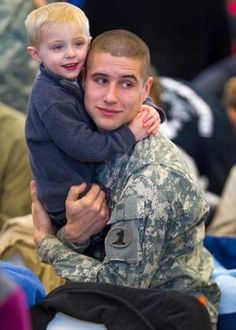 Pfc. Taylor Lord and his son, Trevor, 3, hold each other tight before the ceremony starts. The Delaware unit will travel to western Kandahar Province to spend nine months mentoring and training the Afghan National Police.