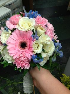 Bridal bouquet with pink gerbers, white spray roses and blue delphinium