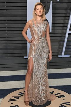 Hailey Baldwin in a drapped rose gold and silver #AtelierVersace Metal Mesh evening dress with front split featuring sparkling scale-effect details at the the #VFOscars party. #VersaceCelebrities Versace.com