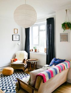 Moody & Modern Windows: Black Curtains // this room features a bunch of my favorites: paper lantern, hanging plant, black and white rug, colorful throw on sofa.  I'm ready to move in!