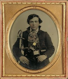hand-colored ambrotype portrait of a Confederate soldier in uniform with a cavalry sword and revolver